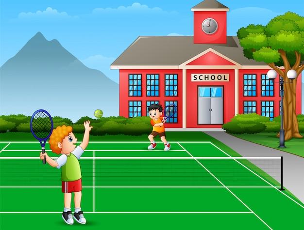 Występują chłopcy grający w tenisa na boisku szkolnym