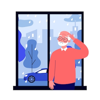 Wzburzony starszy mężczyzna stoi blisko okno i patrzeje deszcz