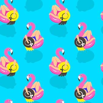 Wzór z dziewczynami na nadmuchiwanym różowym flamingu w lecie pływa i odpoczywa.
