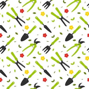 Wzór z narzędziami ogrodniczymi, łopatą, sekatorem, nożyczkami oraz kwiatami i liśćmi.