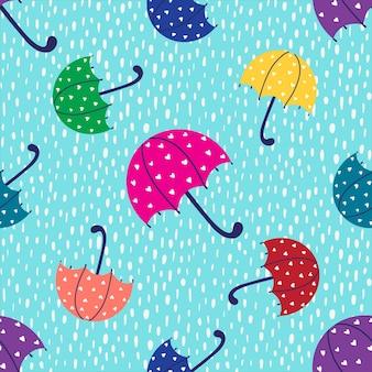 Wzór z wielobarwnym parasolem i kroplami deszczu na niebieskim tle