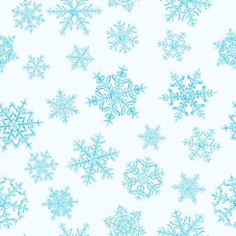Wzór złożonych świątecznych płatków śniegu w jasnoniebieskich kolorach na białym tle