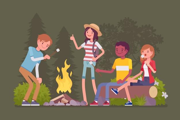 Zabawa na świeżym powietrzu przy ognisku. szczęśliwi młodzi przyjaciele na obozie lub pikniku, ciesz się pieczeniem ptasie mleczko przy ognisku, siedzeniem przy ognisku na plaży w nocnym lesie, ogrzewaniem i rozmową. ilustracja kreskówka styl