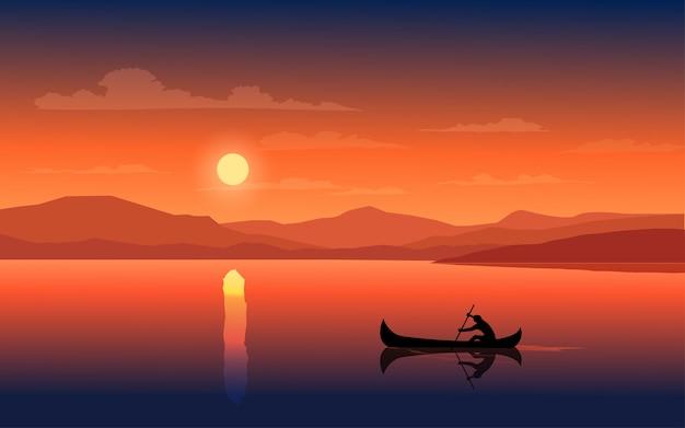 Zachód słońca w jeziorze z człowiekiem na łodzi