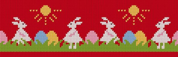 Zajączek i jajka w trawie na wzór dzianiny seamles. wesołych świąt wielkanocnych czerwony nadruk z królikami.