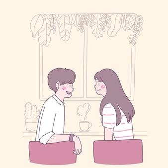 Zakochani młodzi ludzie siedzą na krzesłach i piją kawę przy oknie.