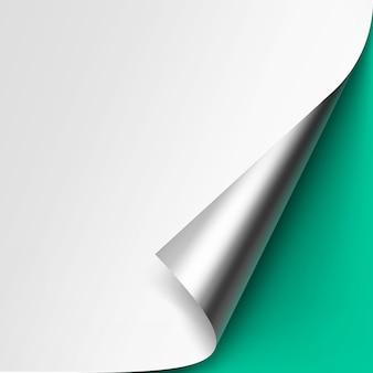 Zakręcony róg metalic silver białego papieru z cieniem makiety zamknij się na białym tle na jasnozielonym tle mięty