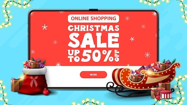 Zakupy online, wyprzedaż świąteczna, do 50% zniżki, baner rabatowy z dużym tabletem z ofertą i przyciskiem na ekranie oraz sanie świętego mikołaja i torba z prezentami