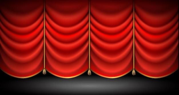Zamknięte czerwone zasłony ze złotymi sznurkami i frędzlami stoją na tle opery lub teatru