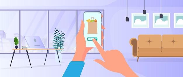 Zamów jedzenie i produkty przez telefon. zamów jedzenie w domu. jedzenie, ręka trzyma smartfon.