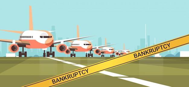 Zaparkowany samolot terminal lotniska z żółtą taśmą bankructwa koronawirusa pandemiczna koncepcja kwarantanny