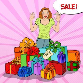 Zaskoczona kobieta pop-artu z ogromnymi pudełkami na prezenty i komiksową sprzedażą bąbelków.