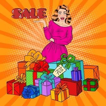 Zaskoczona kobieta pop-artu z ogromnymi pudełkami na prezenty i sprzedażą tekstu komiksowego.