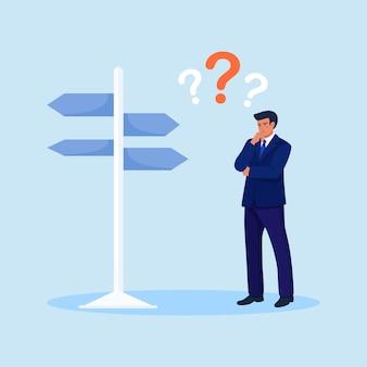 Zdezorientowany biznesmen na skrzyżowaniu patrzy na tablicę znak wybierając kierunek. zamyślony człowiek stojący i podejmowania decyzji biznesowych. osoba wybierająca strategię pracy na sukces. życiowe wybory, pytania dylemat