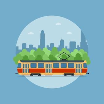 Zdjęcie tramwaju przed drzewami i duża sylwetka miasta