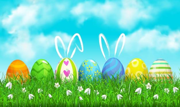 Zdobione jajka z ręcznie rysowanymi uszami królika na zielonej trawie pod niebieskim pochmurnym niebem