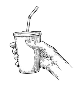 Żeńska ręka trzyma papierową czerwoną filiżanki colę z słoma, nakrętka.