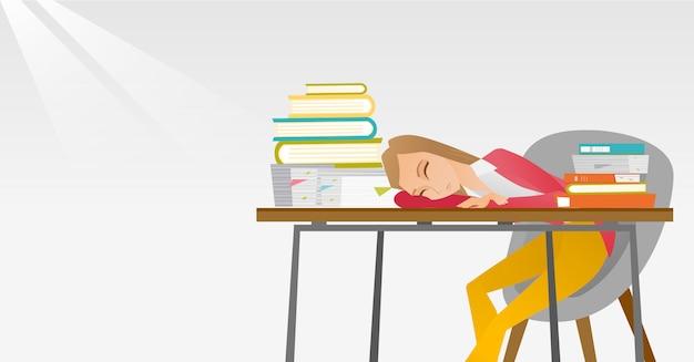 Żeński uczeń śpi przy biurkiem z książką.