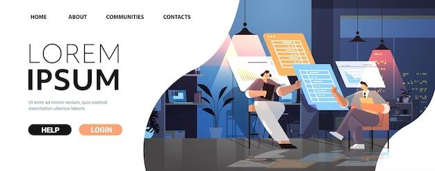 Zespół biznesmenów analizujący dane statystyczne na wirtualnych tablicach pomyślna koncepcja pracy zespołowej ciemna noc wnętrze biura pozioma pełna długość kopia przestrzeń
