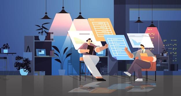 Zespół biznesmenów analizujący dane statystyczne na wirtualnych tablicach pomyślna koncepcja pracy zespołowej ciemna noc wnętrze biura pozioma pełna długość