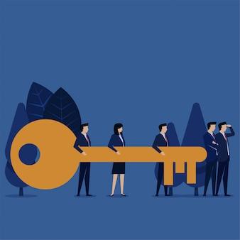 Zespół biznesowy łączy klucz, a menedżer szuka metafory pracy zespołowej.