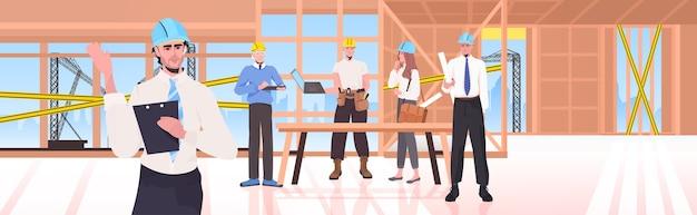 Zespół konstruktorów na placu budowy inżynierowie w kaskach omawiają podczas spotkania koncepcję usługi naprawy niedokończone wnętrze budynku poziomego