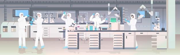 Zespół naukowców w kombinezonach ochronnych trzymających probówki w laboratorium