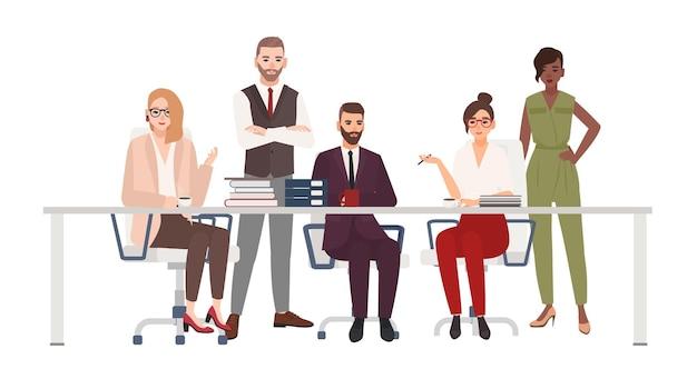Zespół uśmiechniętych pracowników biurowych siedzi przy biurku i omówić kwestie związane z pracą. menedżerowie płci męskiej i żeńskiej podczas burzy mózgów