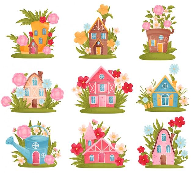 Zestaw bajecznych domków w postaci konewek, butów, doniczki wśród kwiatów i trawy.