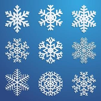 Zestaw białych płatków śniegu w różnych formach z cieniami na niebieskim tle