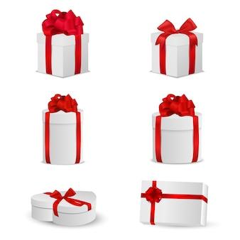 Zestaw białych pudeł z czerwonymi kokardkami i wstążkami.