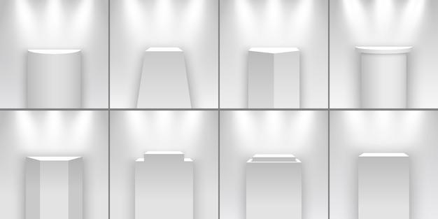 Zestaw białych stoisk wystawienniczych oświetlonych reflektorami. cokoły. podium.