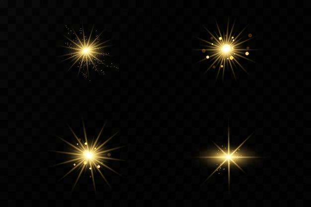 Zestaw błysków, świateł i błyszczy na przezroczystym tle. jasne złote błyski i spojrzenia. streszczenie złote światła izolowane jasne promienie światła