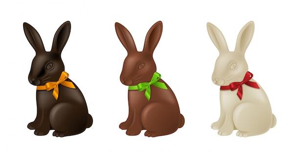Zestaw czekoladowych królików wielkanocnych z kolorowymi kokardkami. króliczki z ciemnej, mlecznej i białej czekolady