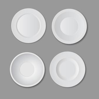 Zestaw czterech pustych białych talerzy na białym tle na szarym tle, widok z góry