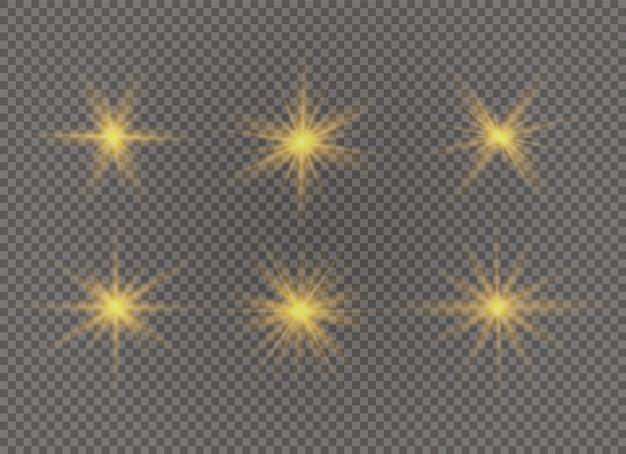 Zestaw jasnej gwiazdy. żółte świecące światło wybucha na przezroczystym tle. przezroczyste świecące słońce.