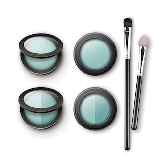 Zestaw jasnoniebieskich szarych cieni do powiek w okrągłej czarnej przezroczystej plastikowej obudowie z aplikatorami pędzli do makijażu widok z góry na białym tle