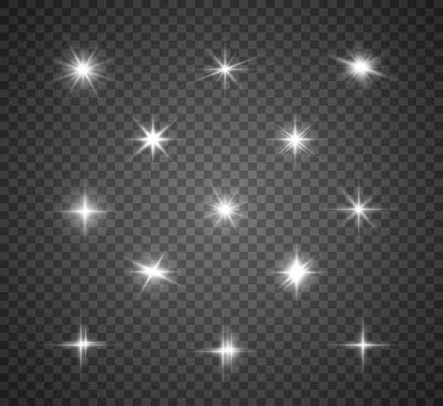 Zestaw jasnych pięknych gwiazd. efekt świetlny. jasna gwiazda. biały brokat mieni się ze specjalnym efektem świetlnym. błyszczy na przezroczystym tle.