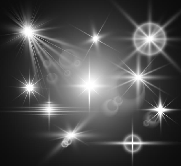 Zestaw jasnych, pięknych gwiazd. efekt świetlny. jasna gwiazda. piękne światło do ilustracji. białe iskierki błyszczą specjalnym efektem świetlnym.