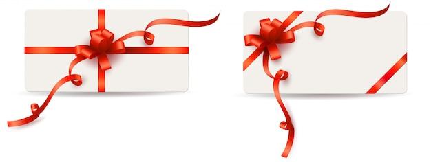 Zestaw kart podarunkowych z czerwonymi kokardkami i kręconymi wstążkami na białym tle