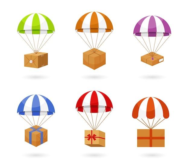 Zestaw kolorowych spadochron przewożących brązowe pudełka do dostawy na białym tle.