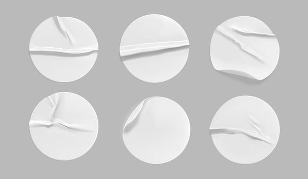 Zestaw makiet białych okrągłych zmiętych naklejek. samoprzylepna biała papierowa lub plastikowa etykieta samoprzylepna z wklejonym, pomarszczonym efektem na szarym tle.