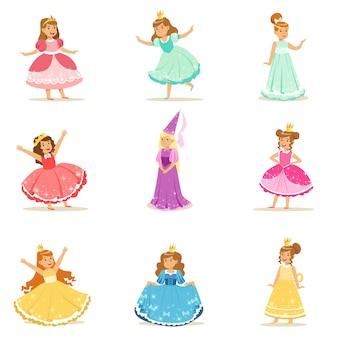 Zestaw małych dziewczynek w stroju księżniczki w koronie i fantazyjnej sukience z uroczymi dziećmi przebranymi za ilustracje królewskie