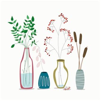 Zestaw minimalistycznych eleganckich szklanych wazonów z suszonymi roślinami, kwiatami i liśćmi skandynawskiego hygge