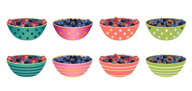 Zestaw misek ze świeżymi jagodami i orzechami.