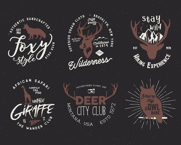 Zestaw odznak dzikich zwierząt. zawarte kształty żyrafy, sowy, lisa i jelenia. zapas odizolowywający na ciemnym tle.