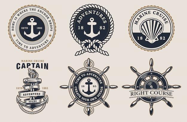 Zestaw odznak żeglarskich z kierownicą, kotwicą, muszelką na jasnym tle.
