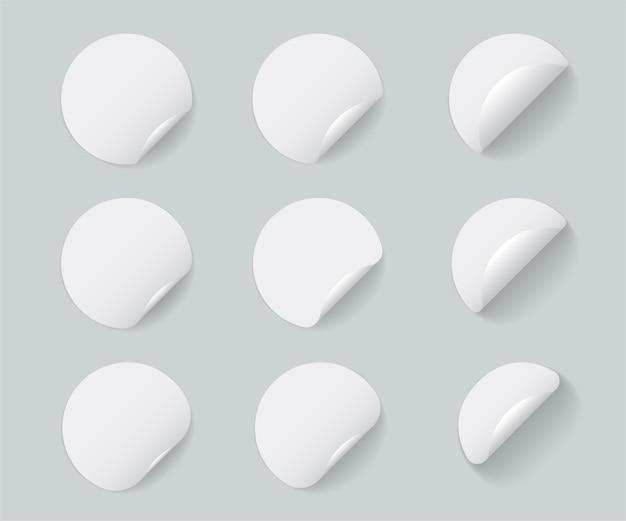 Zestaw okrągłych białych naklejek z zawiniętym rogiem i cieniami.