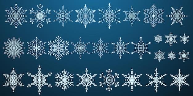 Zestaw pięknych złożonych świątecznych płatków śniegu, biały na niebieskim tle