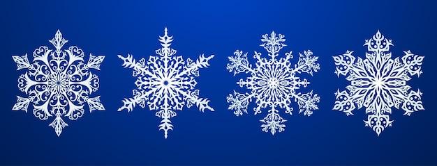 Zestaw pięknych złożonych świątecznych płatków śniegu, białych na niebieskim tle